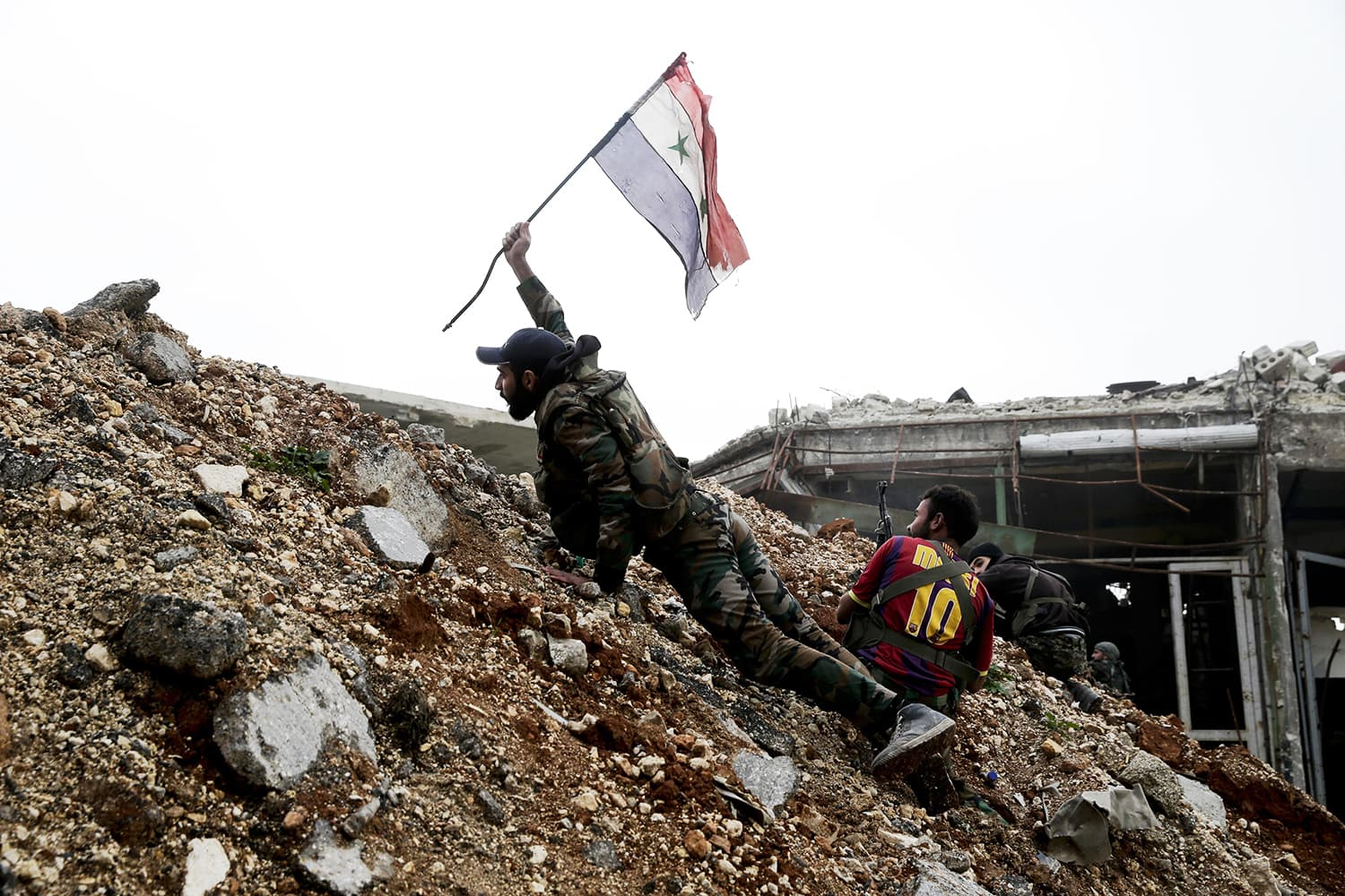 A Syrian army soldier places a Syrian national flag during a battle with rebel fighters at the Ramouseh front line, east of Aleppo, Syria, Monday, Dec. 5, 2016. ─ AP/File