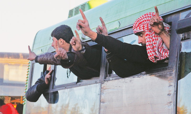 Evacuees raise their fingers as their bus arrives in the town of Al Rashideen on Thursday.—Reuters