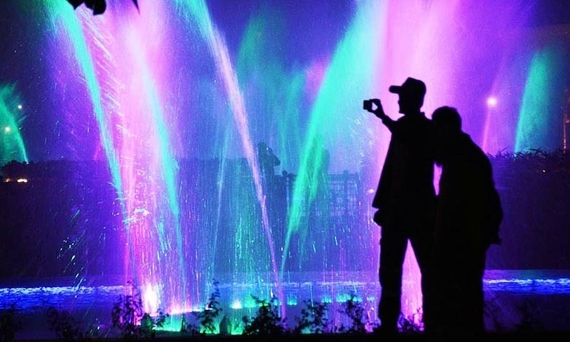 Visitors take pictures of beautiful moving fountains installed with colour lights at Greater Iqbal Park. ─Online