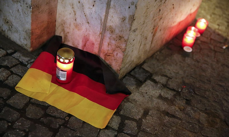 A candle is burning on a German national flag near the attack site.— Reuters