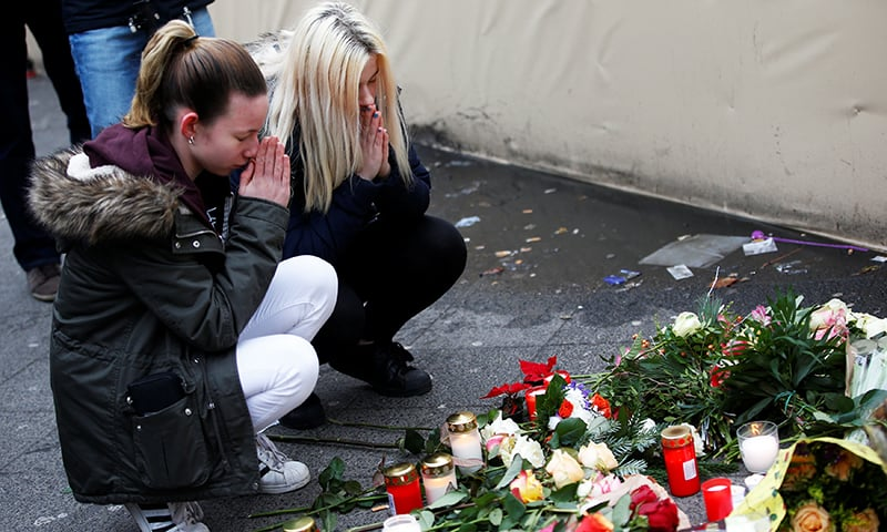 Women mourn at the scene where a truck ploughed into a crowded Christmas market. -Reuters