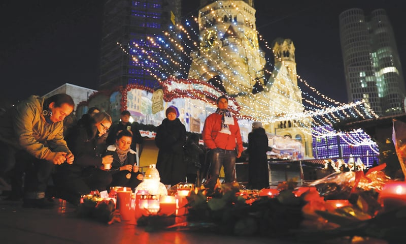 BERLIN: People light candles on Wednesday at a makeshift memorial near the site of the assault.— AFP