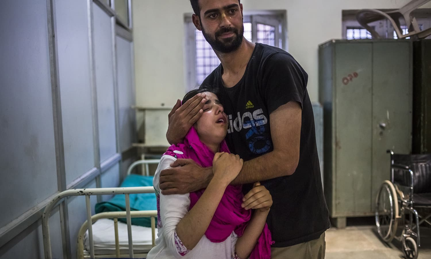A Kashmiri youth accompanying a family member holds Khobu Zainab, 15, and who is unrelated, as she reacts as medical staff try to sedate her during a panic attack in the casualty ward of the Psychiatric Diseases Hospital in Srinagar. ─AFP