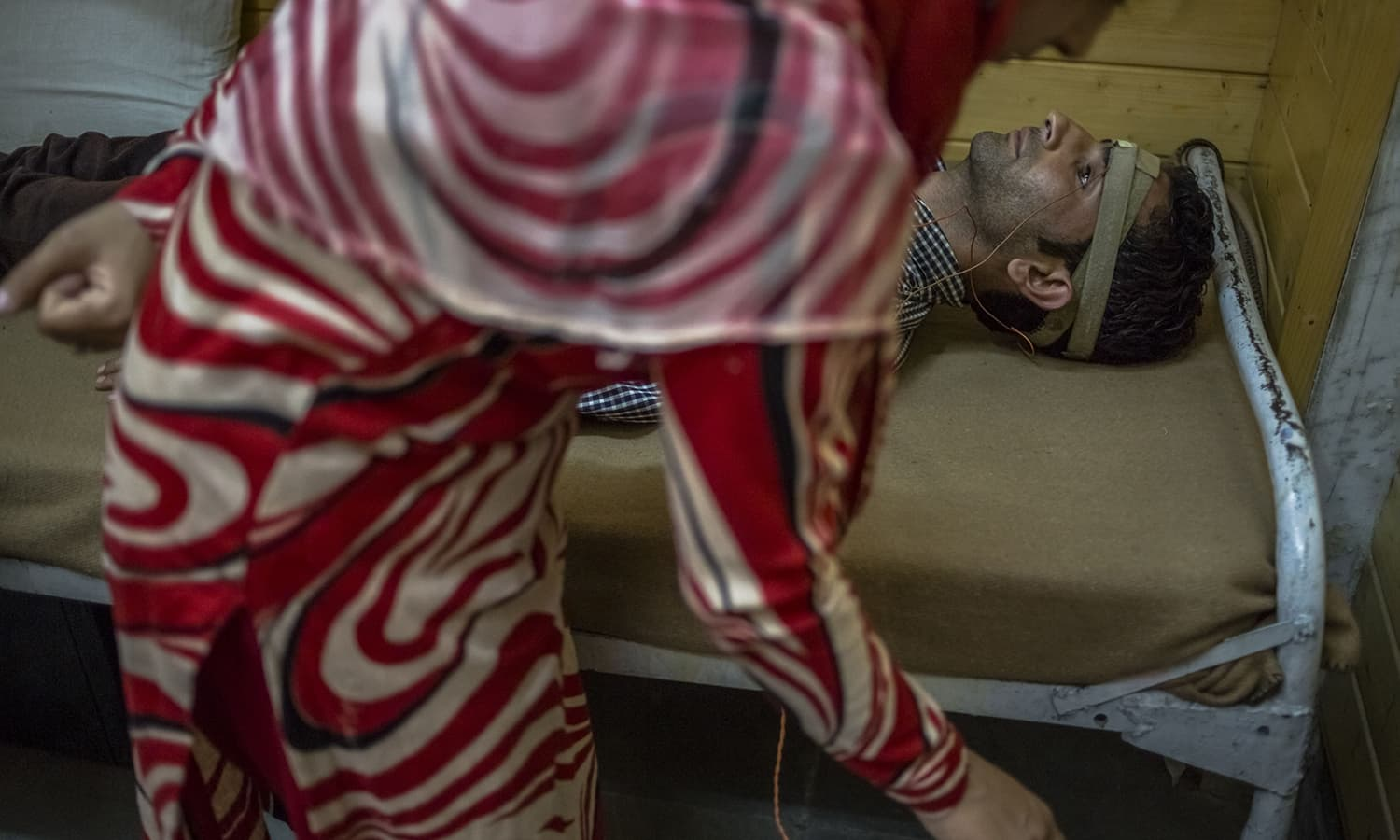 A Kashmiri patient who has been suffering from symptoms of depression and anxiety undergoes a form of electro-convulsive therapy by a member of medical staff at the Psychiatric Diseases government hospital in Srinagar.─AFP