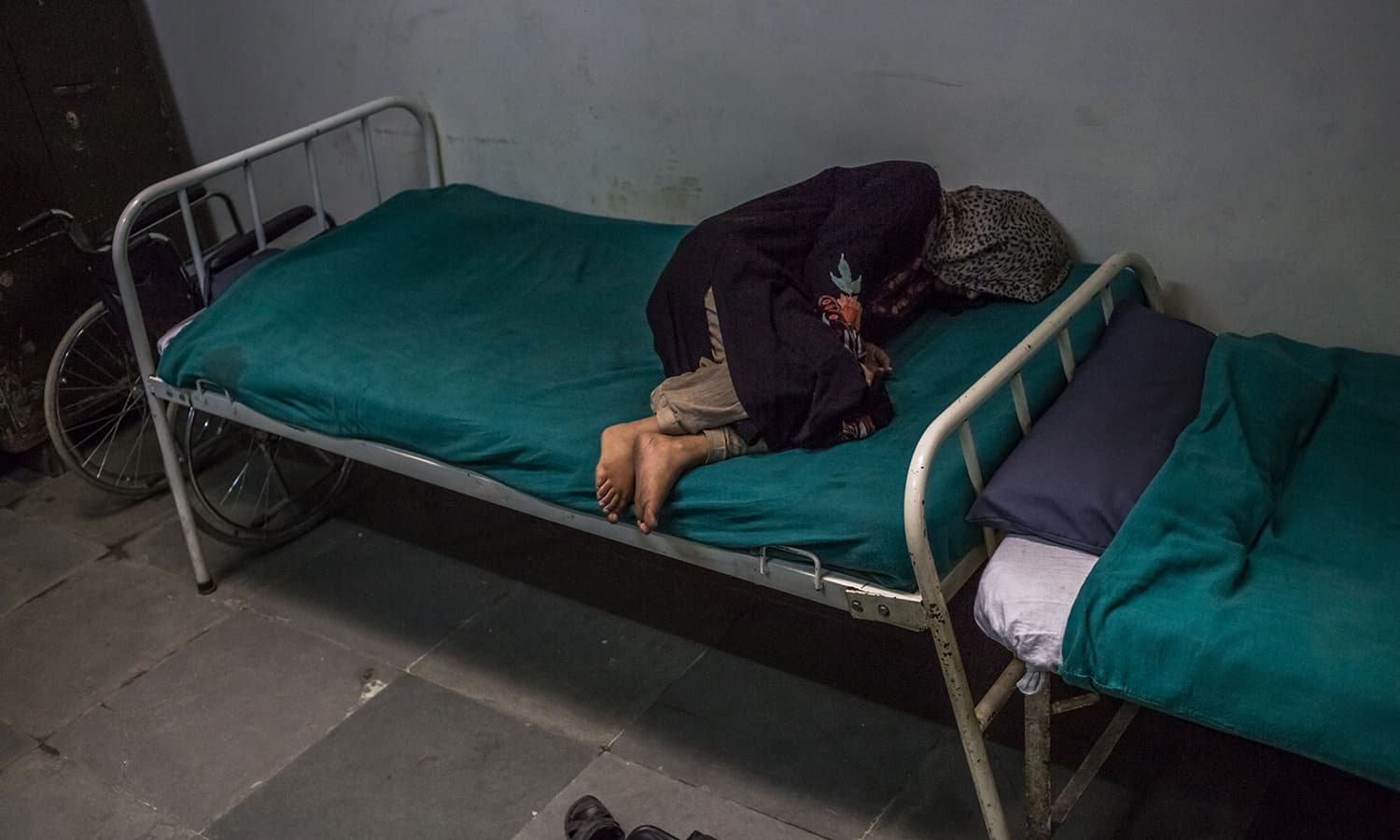 Patient Masrat Naz, 45, and who is suffering from symptoms of schizophrenia, lies on a bed as she periodically shouts to medical staff after being brought by relatives to the casualty ward at the Psychiatric Diseases hospital in Srinagar.─AFP
