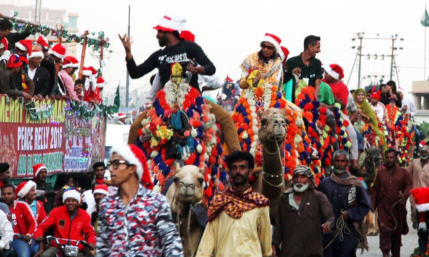 People wearing Santa hats ride camels during the rally. — PPI