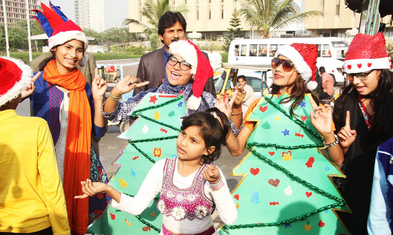 Women in Christmas tree costumes sing carols on the street during the rally.— PPI