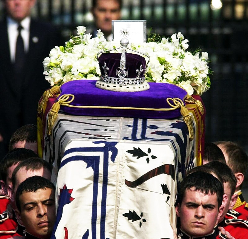 This file photo taken on April 5, 2002 shows the Crown Jewels atop the standard-draped coffin of Queen Elizabeth the Queen Mother as it is taken out of Queen's Chapel, St. James' Palace, in central London, carried by soldiers of the Royal Irish Guards, on its way to Westminster Hall.— AFP