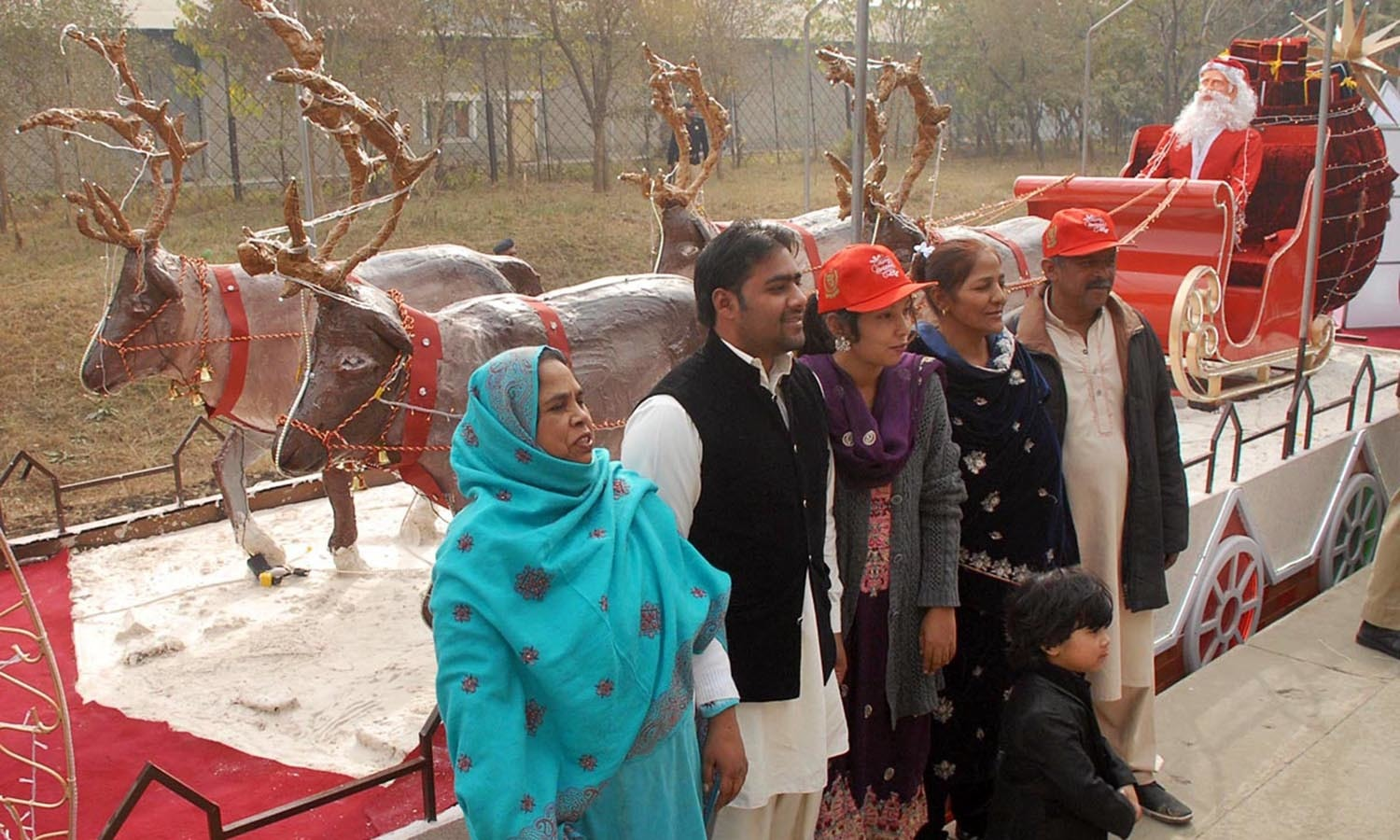 People take pictures with reindeer chariot with Santa Claus during inauguration of Christmas train at Islamabad Railway Station ahead of Xmas.─Online photo by Waseem Khan