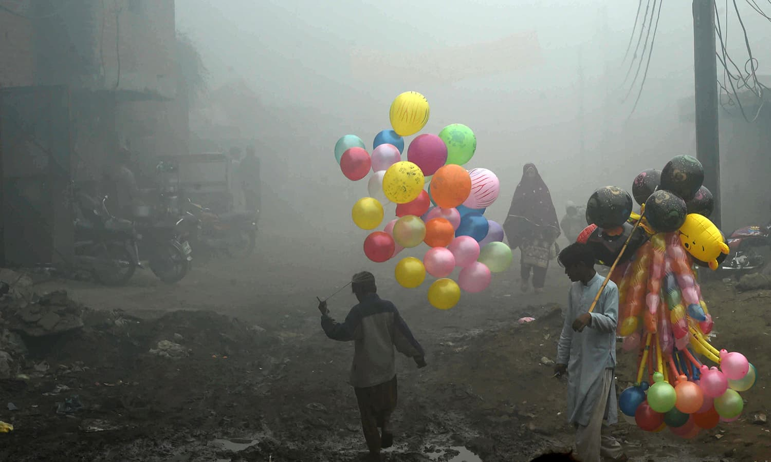 Pakistani balloon vendors cross a street in heavy fog in Lahore. ─AFP