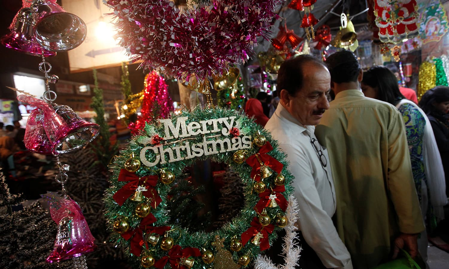 People walk past an artificial decoration wreath hanging outside a shop selling various items for Christmas celebrations in Karachi. ─Reuters