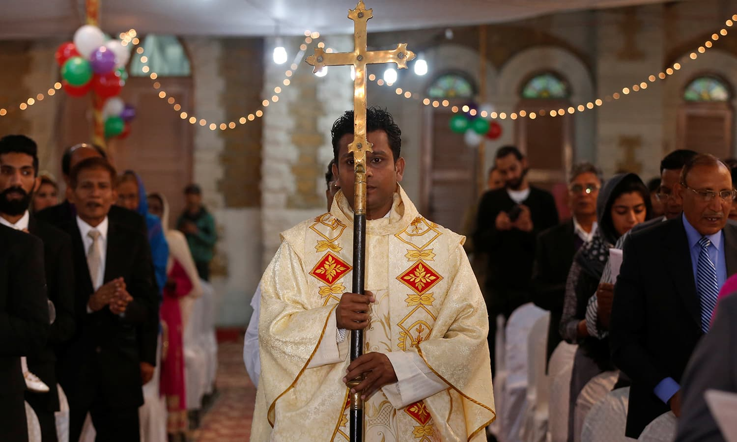 A member of church holds a cross as he walks past people pray during a ceremony on Christmas eve at Central Brooks Memorial Church in Karachi. ─Reuters