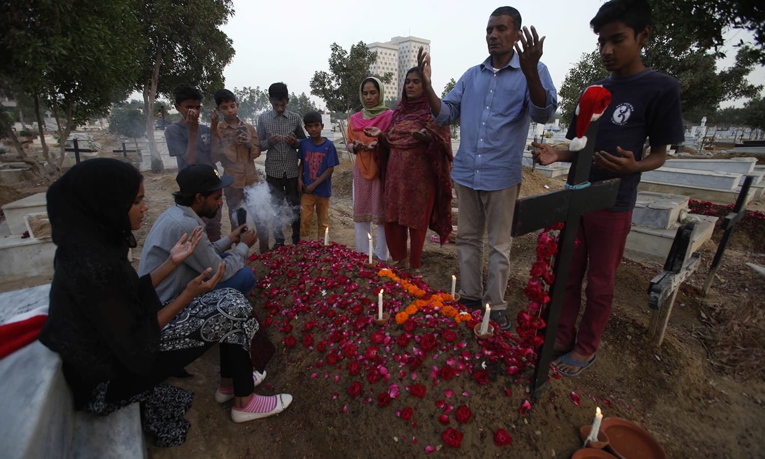 Christians visit a grave of their family member at a graveyard ahead of Christmas in Karachi. ─AP