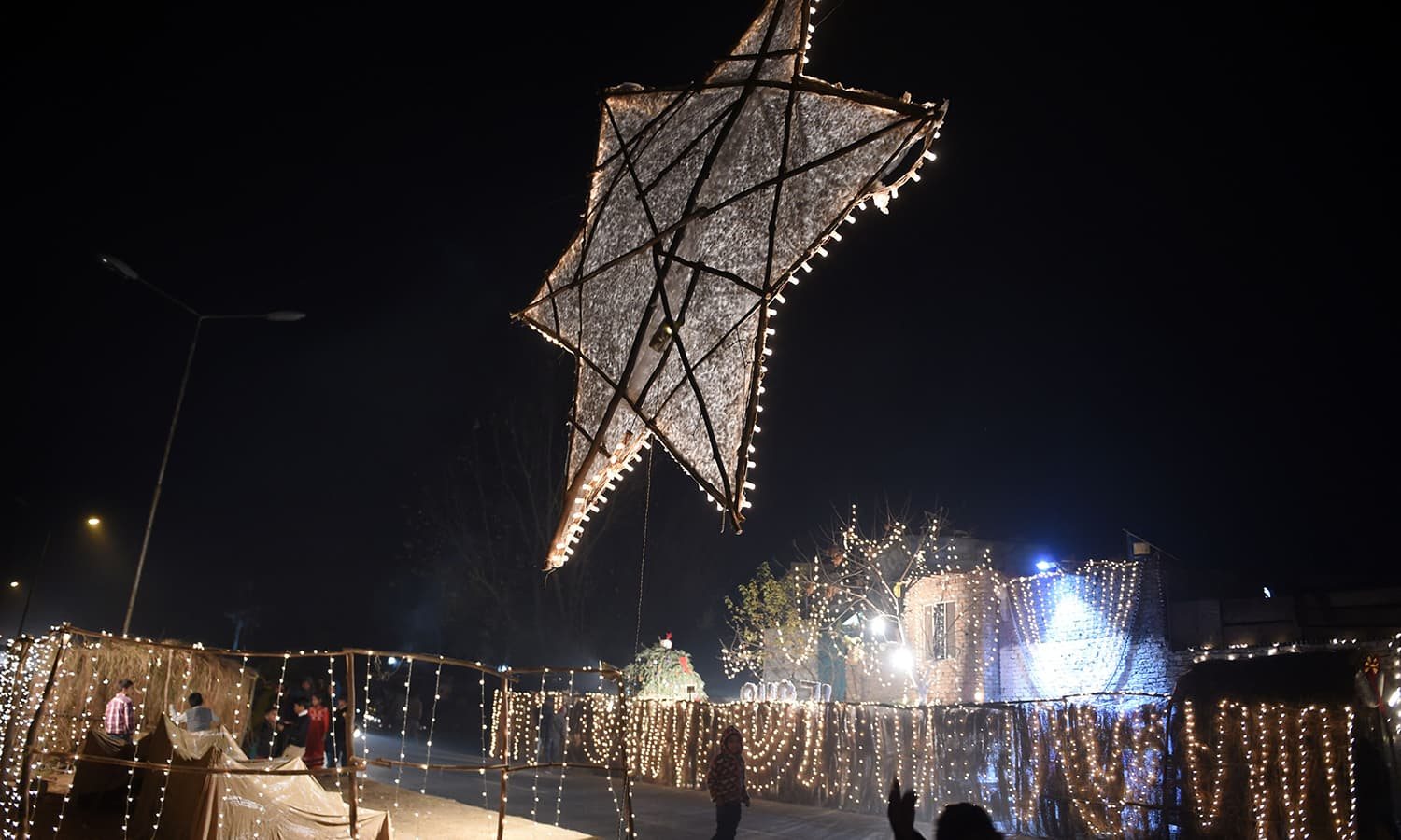 Pakistani Christian children walk past the lights decoration for Christmas celebration in Islamabad.─AFP