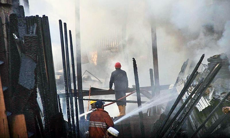 Fire fighters extinguishing fire which erupted in Haji Camp Timber Market. —Online
