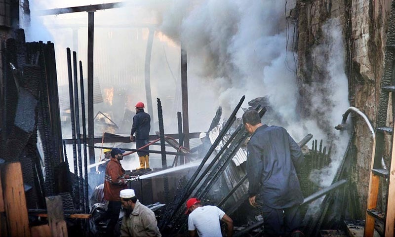 Men salvage wood while fire fighters extinguish fire which erupted in Haji Camp Timber Market. —Online