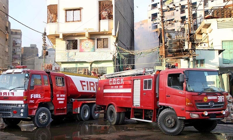 Vehicles of fire brigade seen near a narrow street after fire erupted in timber market. —Online
