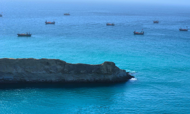 پہاڑیوں سے ایک خوبصورت منظر، ساتھ میں ملاحوں کی کشتیاں بھی نظر آ رہی ہیں — تصویر عباس علی طور
