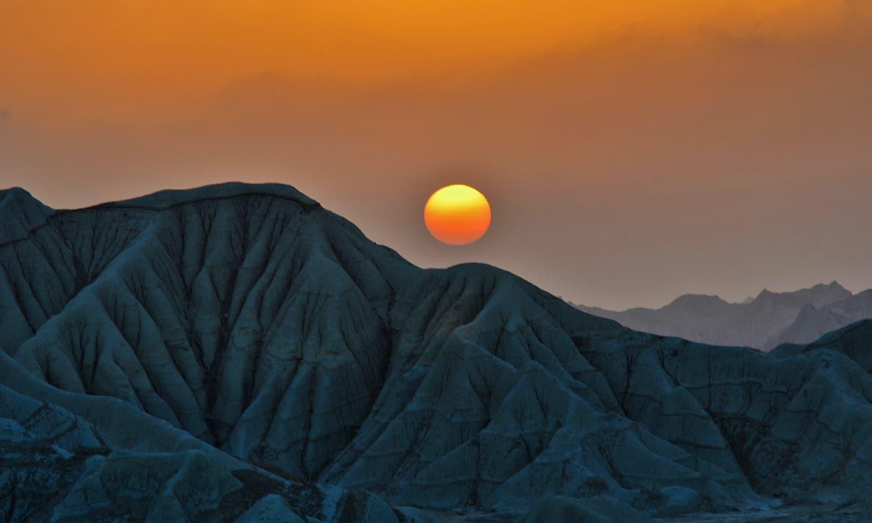 جزیرے کی سات پہاڑیوں سے غروبِ آفتاب کا ایک دلکش نظارہ— تصویر عباس علی طور