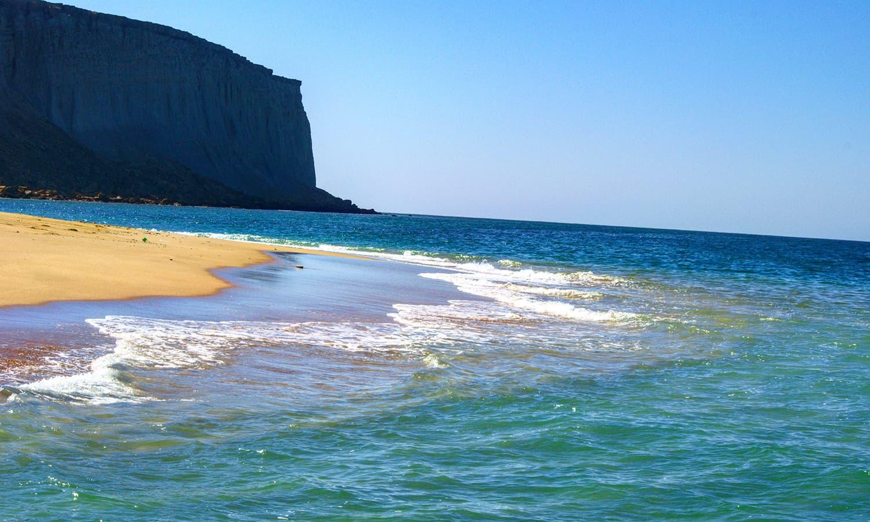 دوپہر میں جزیرے سے ٹکراتا سمندر پرسکون محسوس ہوتا ہے— تصویر عباس علی طور