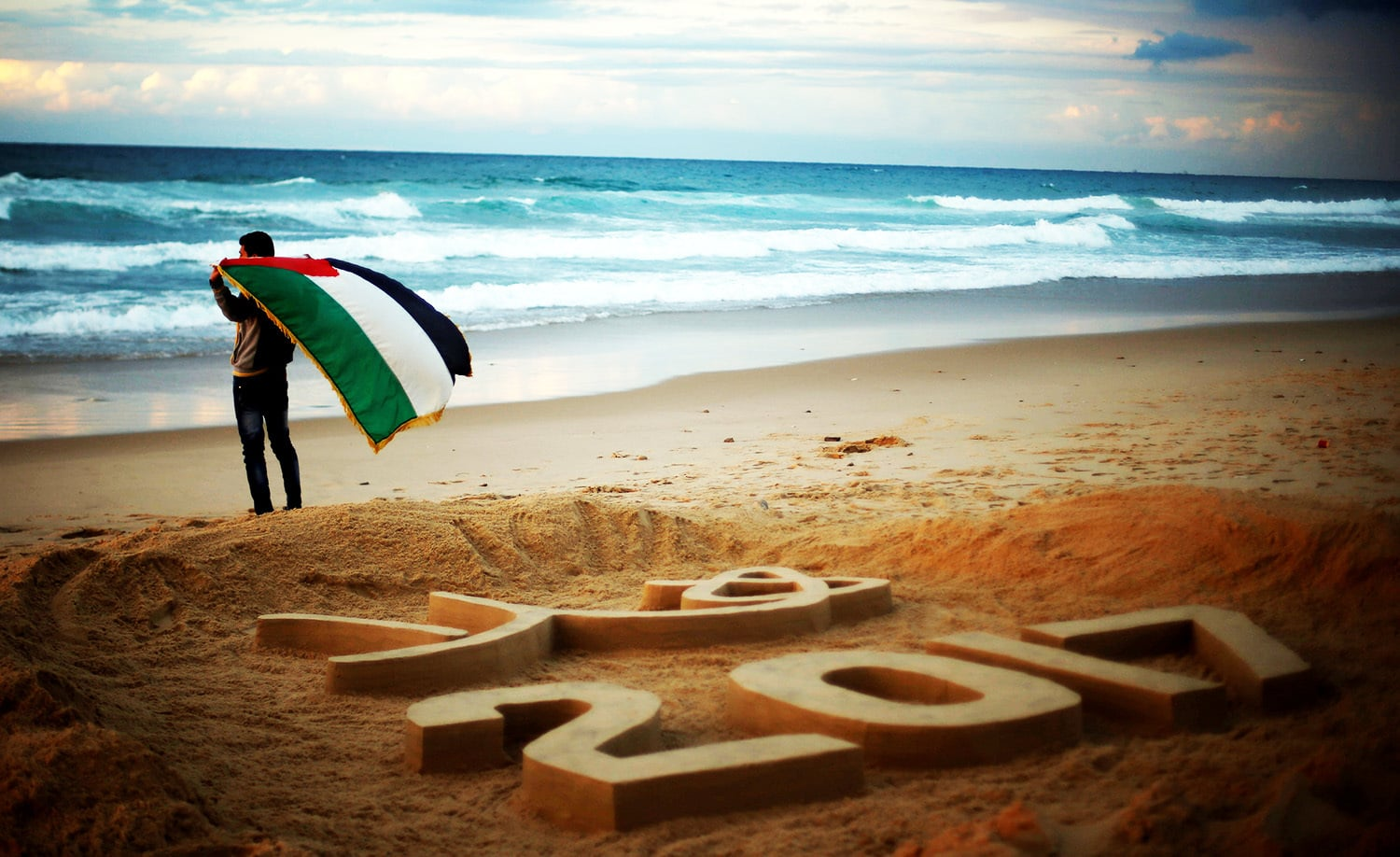 "Palestinian artist Yazed Abu Jarad holds a Palestinian flag after making a sand sculpture that reads ""Welcome 2017"" at a beach in the northern Gaza Strip.—Reuters"
