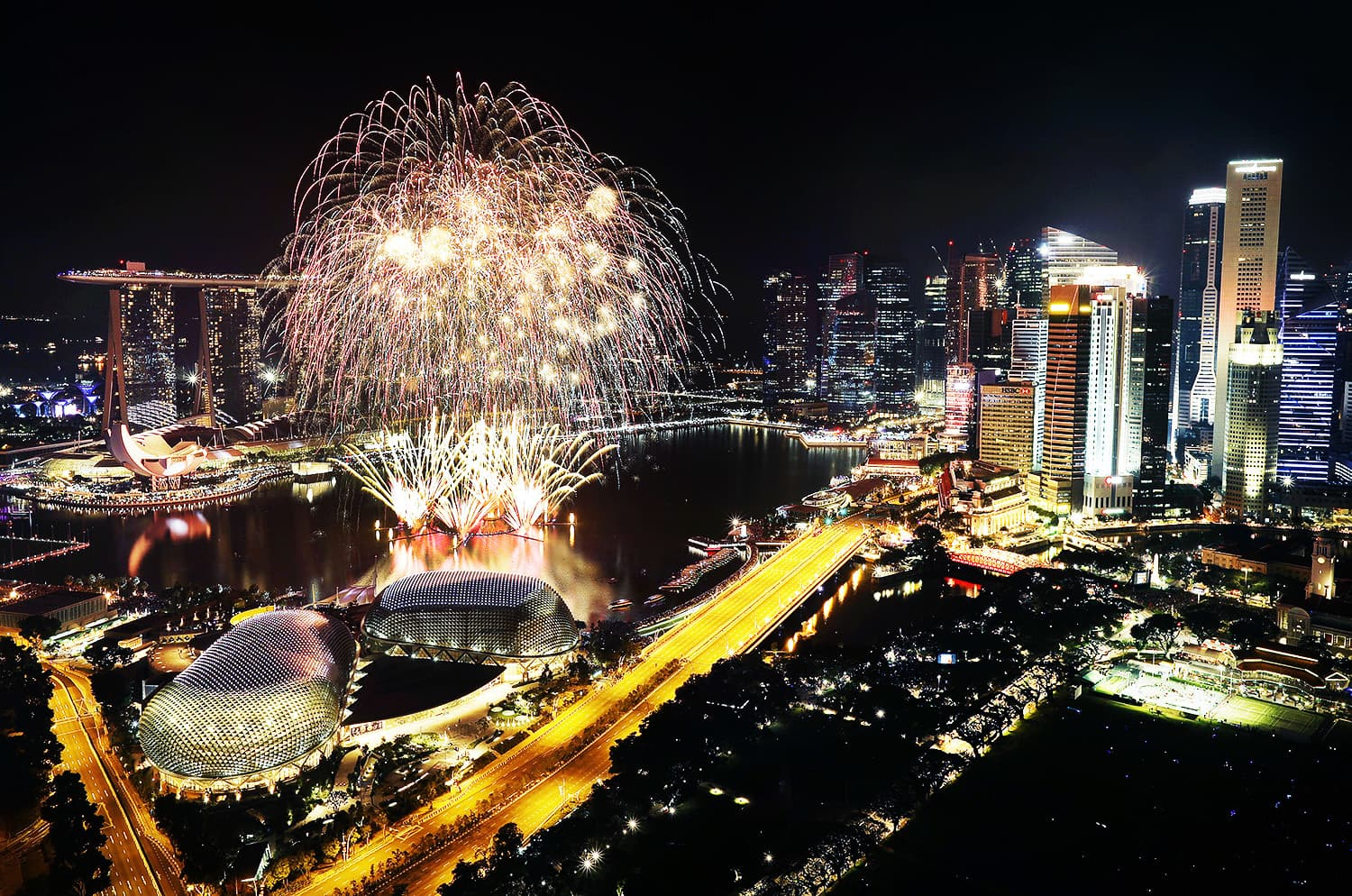 Fireworks explode above Singapore's financial district at the stroke of midnight to mark the New Year's celebrations.—AP