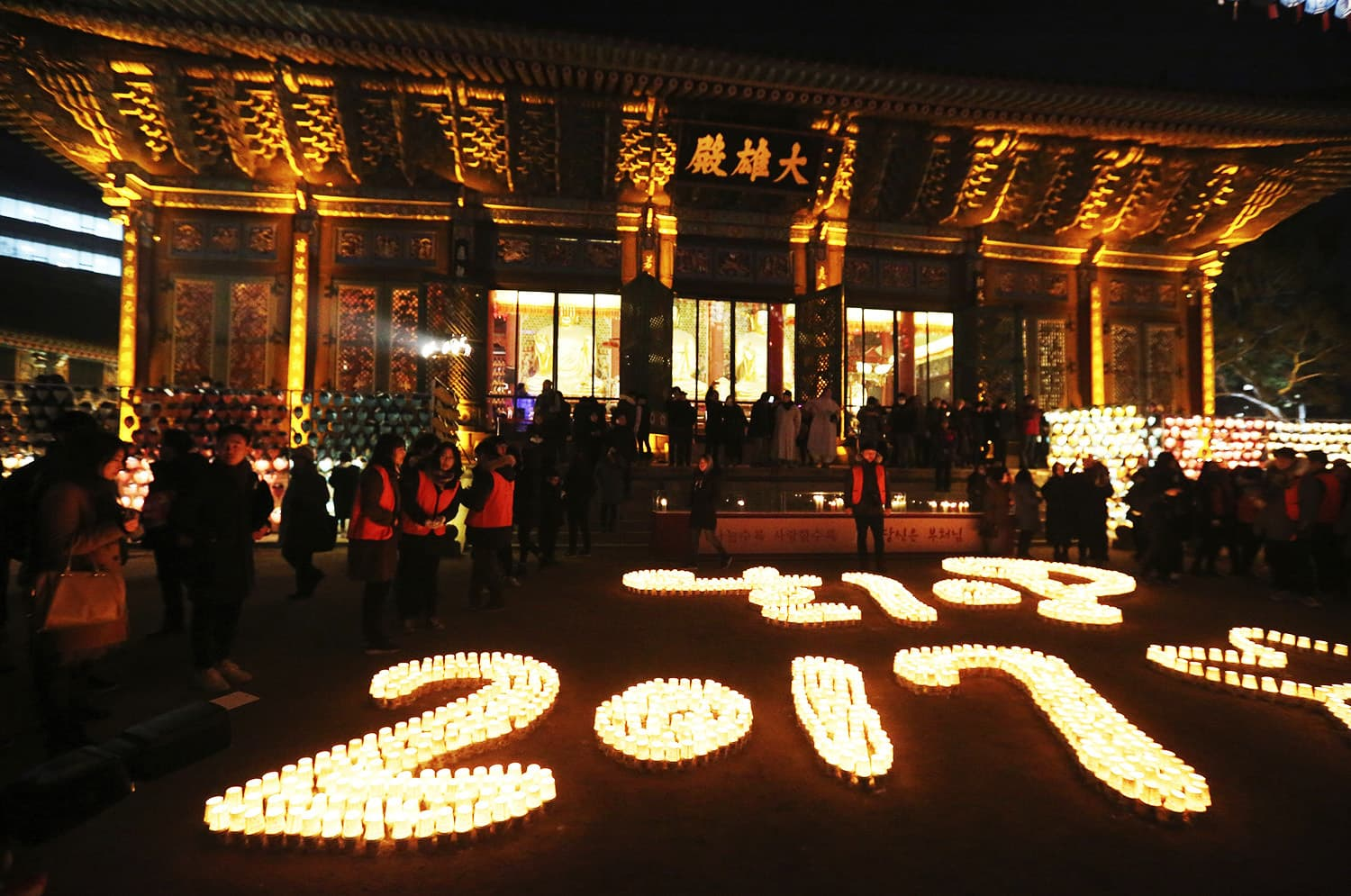 Buddhists light candles during New Year celebrations at Jogye Buddhist temple in Seoul, South Korea.—AP