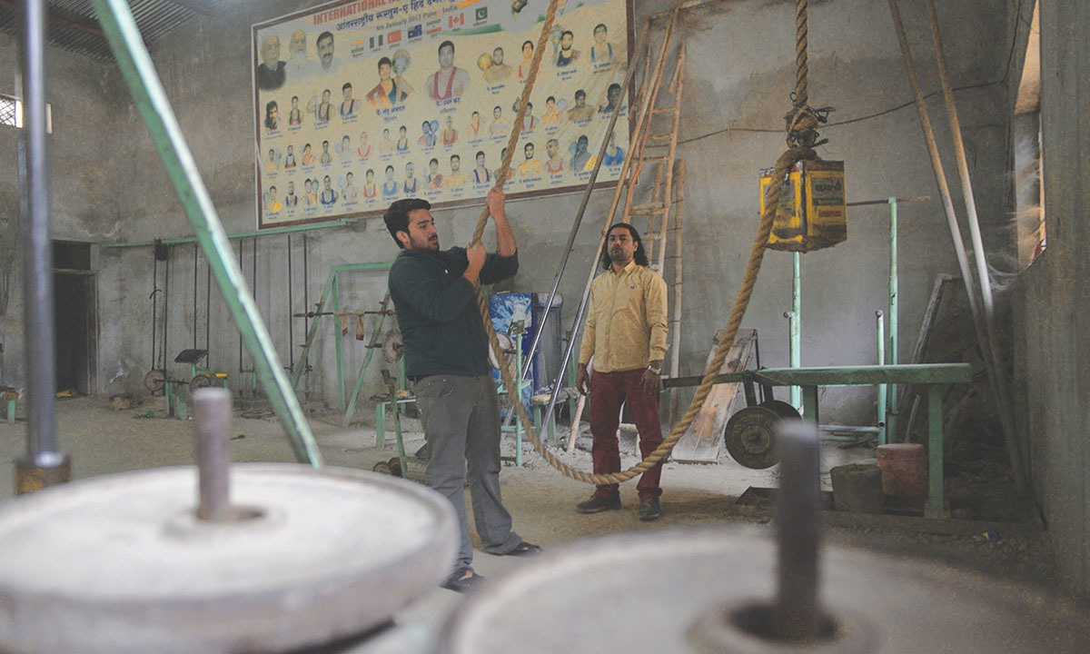 A gym instructor helps his trainee exercise in Gujranwala