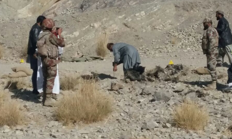 Security officials examine the site of the blast.— DawnNews