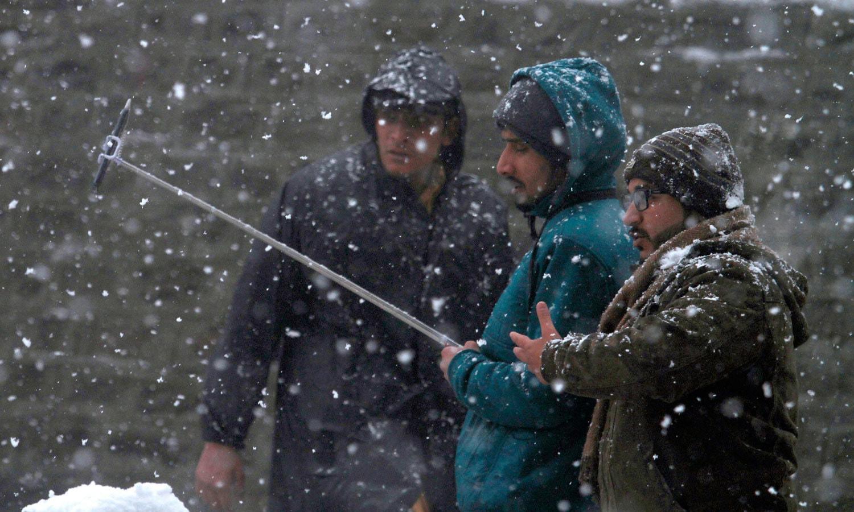 مری میں مقامی سیاح برف باری کے دوران سیلفی لے رہے ہیں — فوٹو: اے پی