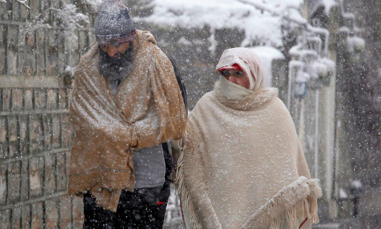 مری میں مقامی افراد پیدل چلتے ہوئے برف باری کے دوران اپنی منزل کی طرف جارہے ہیں — فوٹو: اے پی