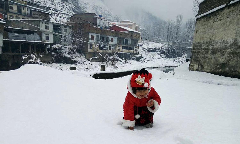 الپوری میں ننھی بچی برف سے کھیل رہی ہے — فوٹو: آن لائن