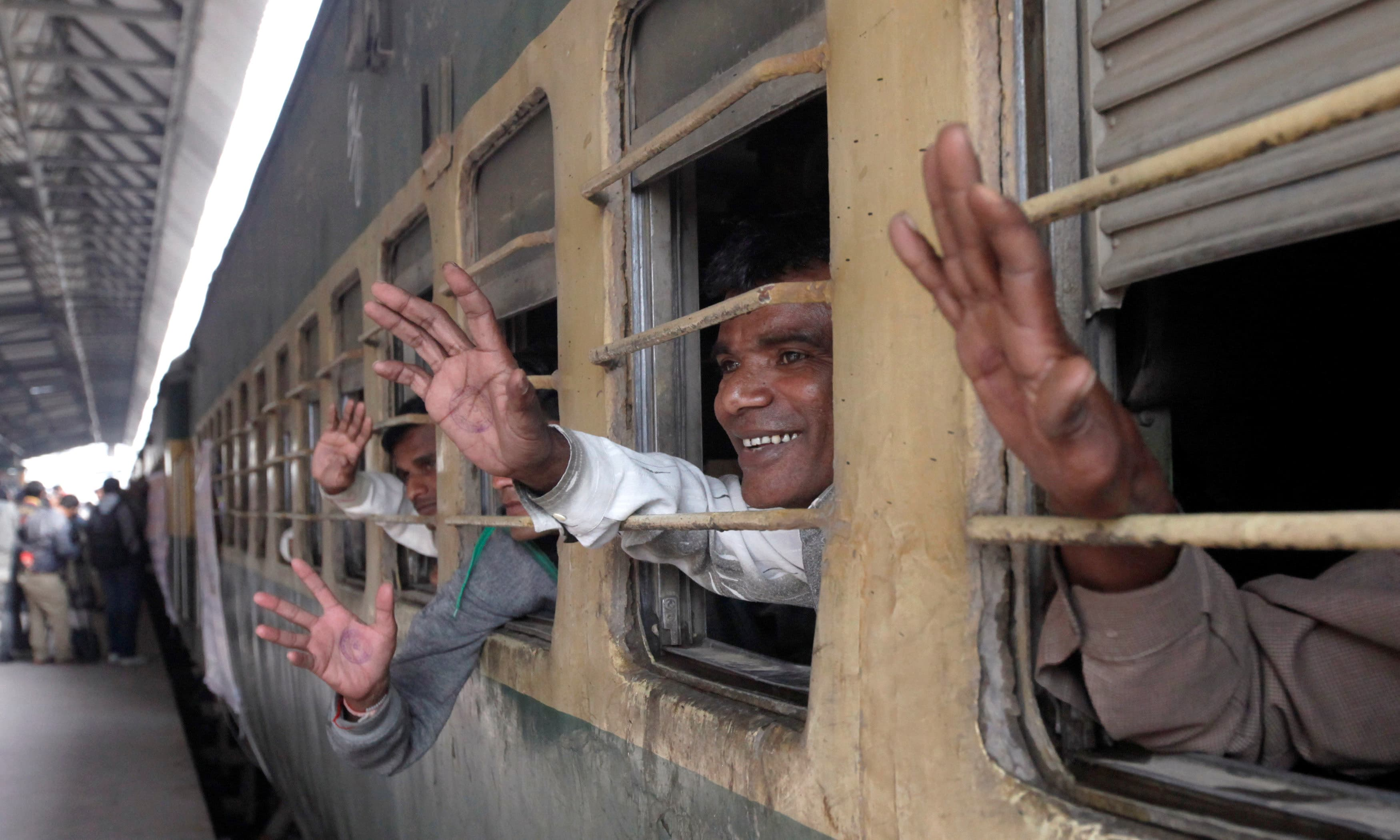 Fishermen from India wave from the windows of a train after their release. —Reuters
