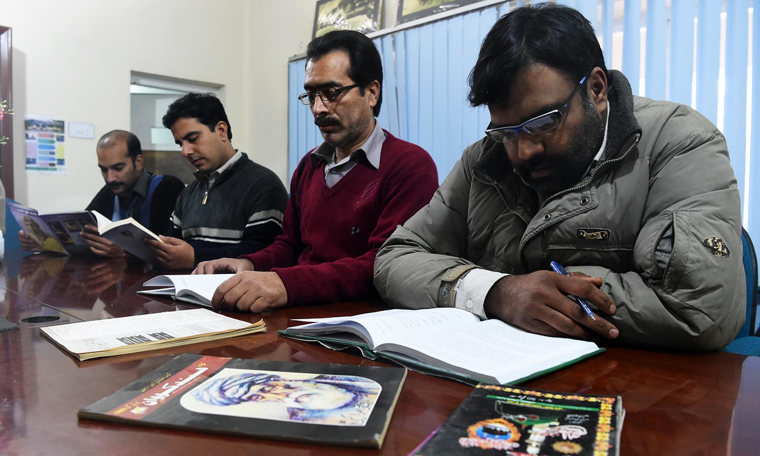 Men read Hindko language books at The Hindko Centre in Peshawar.— AFP