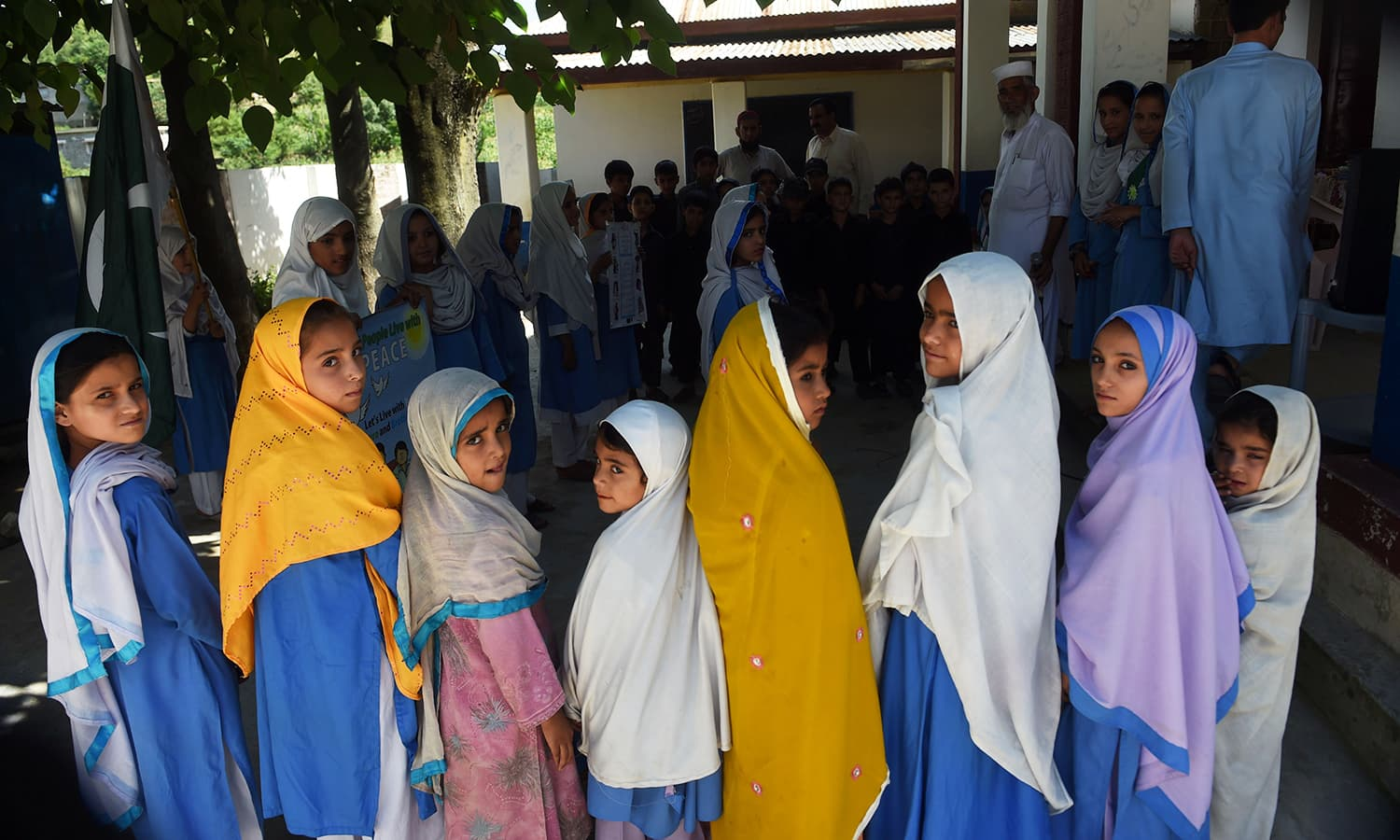 Hindko speaking schoolchildren sing the national anthem at their school in Mansehra.— AFP
