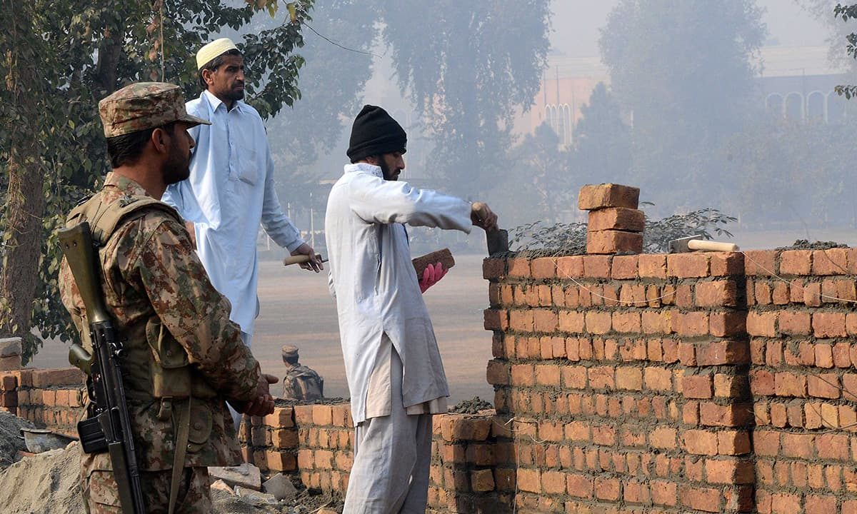 A soldier oversees the rebuilding of Army Public School's boundary wall in Peshawar | White Star