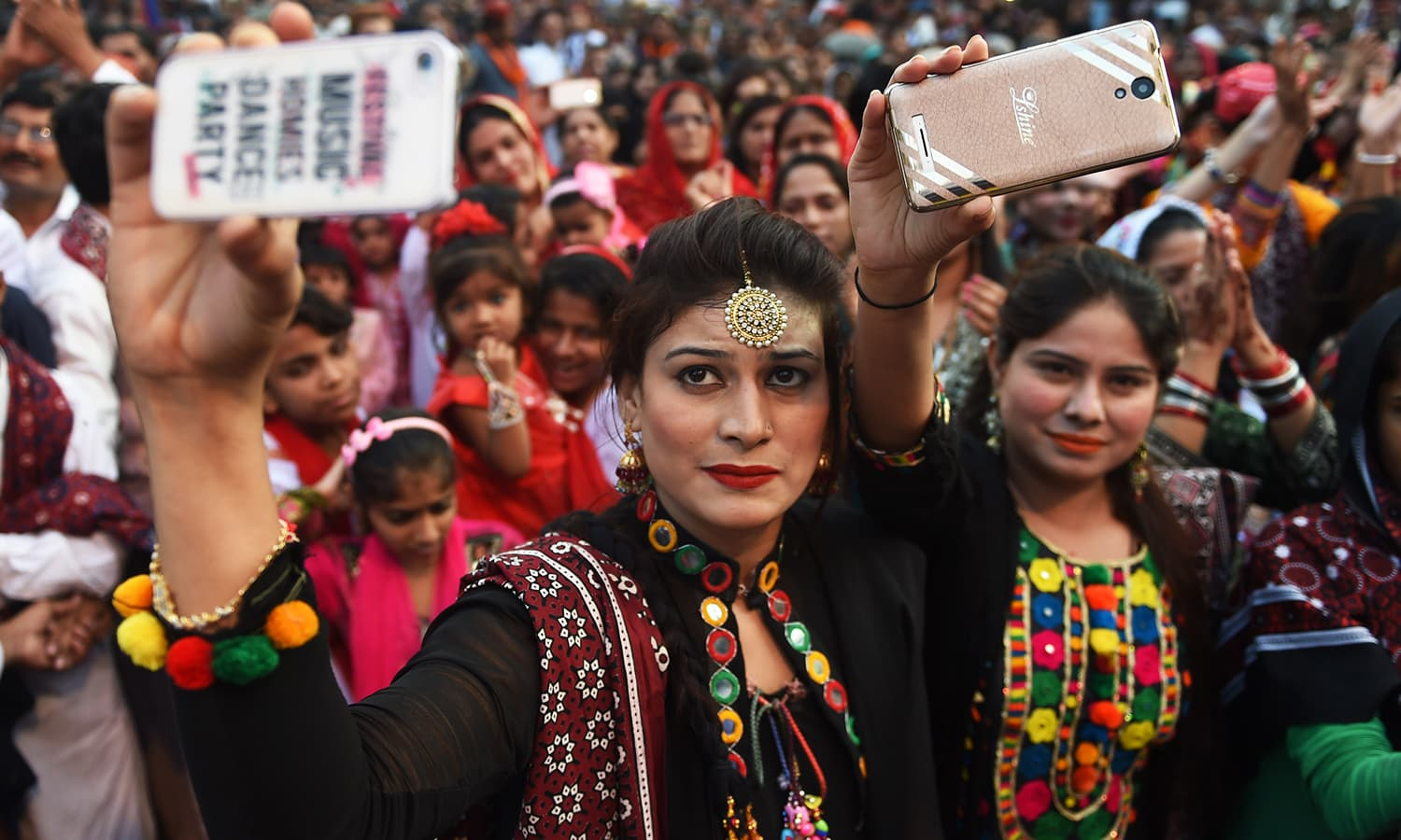Young Sindhi women pose for a 'selfie' as they attend a Sindh Cultural festival in Karachi.— AFP