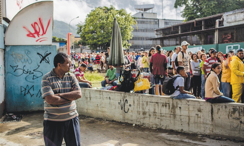 A man waits in line to buy food at a grocery store in La Urbina, Venezuela.— The Washington Post