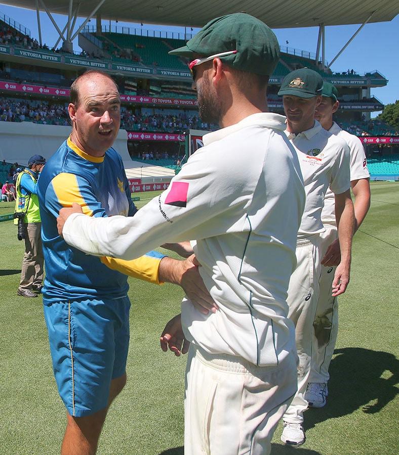 میچ میں شکست کے بعد پاکستان کے کوچ مکی آرتھر آسٹریلین وکٹ کیپر میتھیو ویڈ سے ہاتھ ملا کر مبارکباد دیتے ہوئے— فوٹو: اے ایف پی