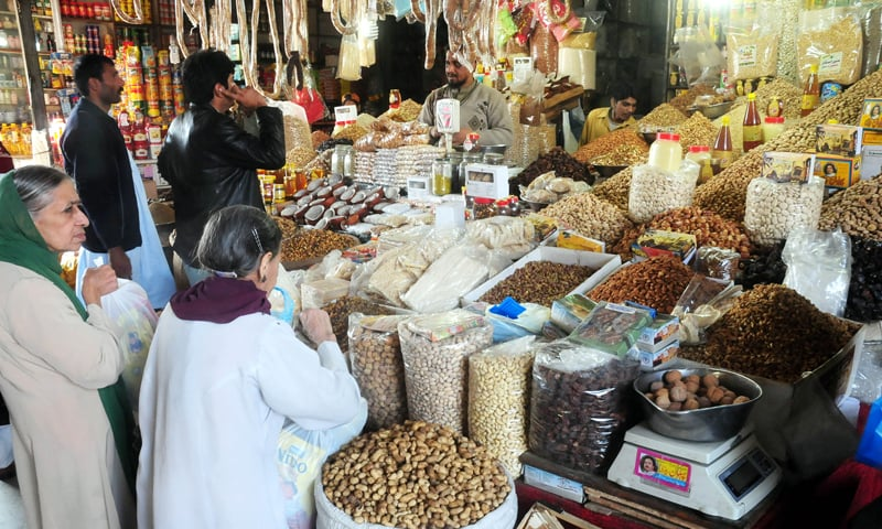 KARACHI: People buying dried fruits from a shop in Empress Market on Saturday.—Fahim Siddiqi/White Star