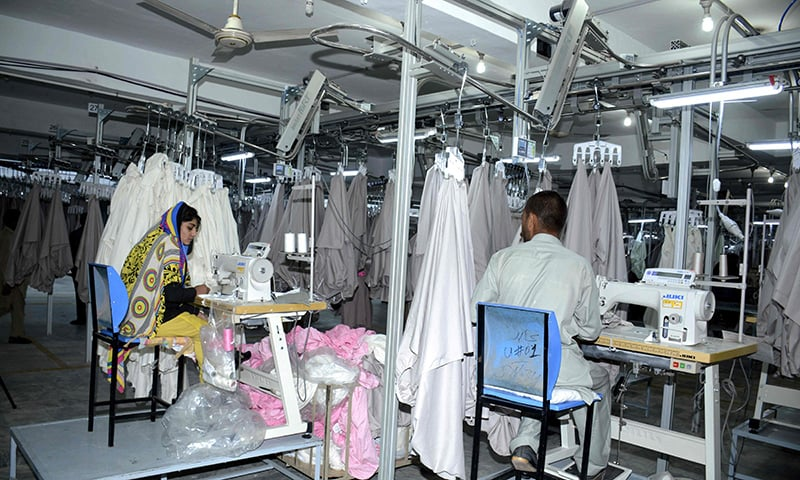 Pakistani machinists work at a textile factory in Faisalabad.─AFP