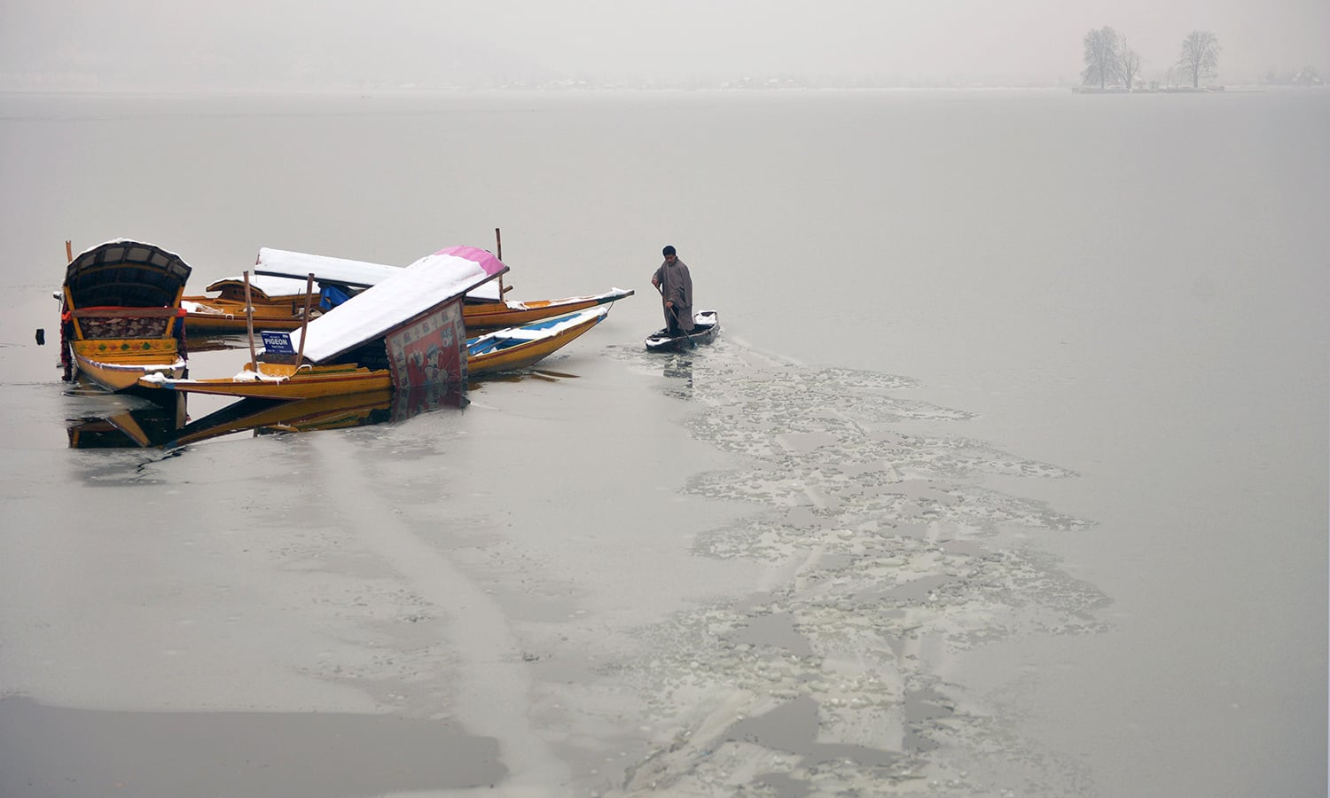 A Kashmiri boatman uses his oar to break the ice layer of the frozen Dal Lake after a heavy snowfall in Srinagar. ─AFP