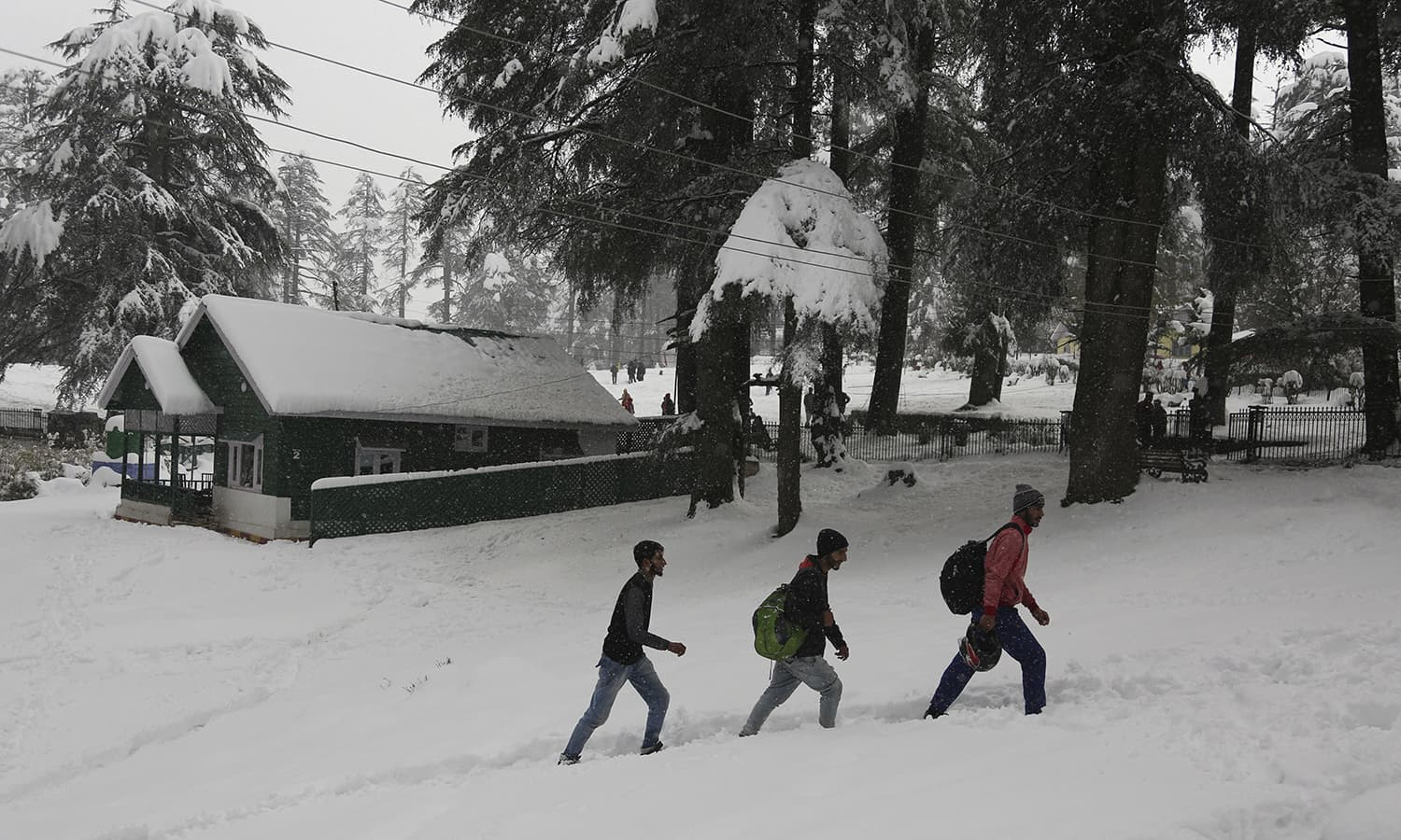 People walk through a snow-covered pathway at Patnitop in Udhampur district of Jammu and Kashmir state.─AP