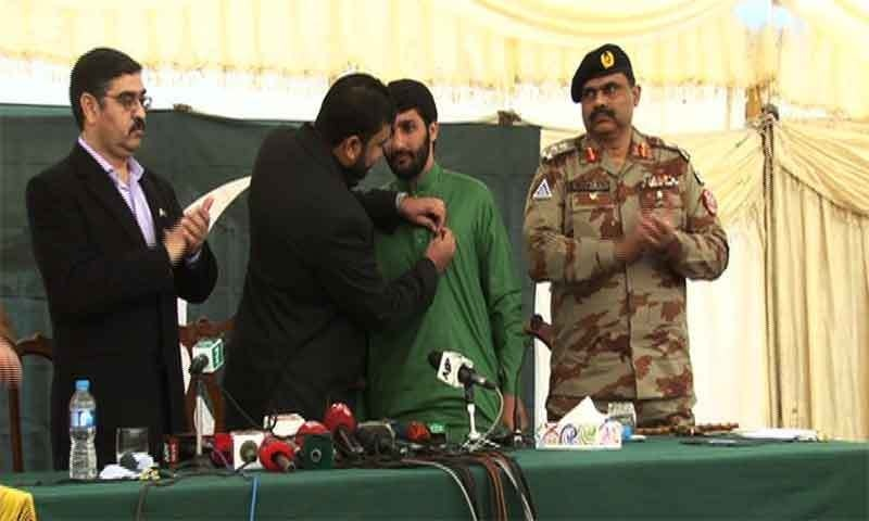 An official pins a Pakistan flag on the surrendering militant's chest — Ali Shah.