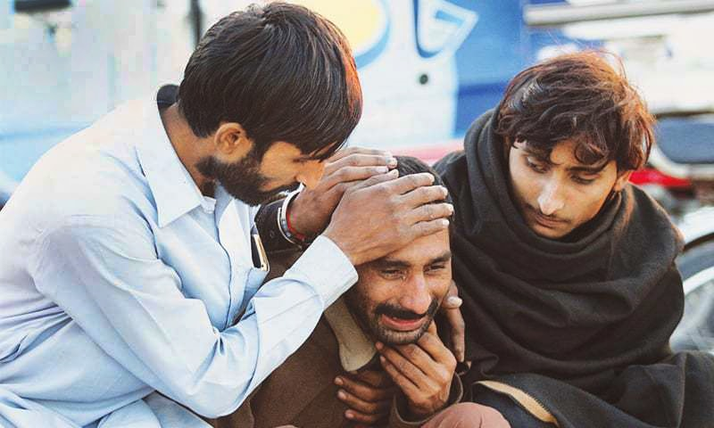 A man breaks into tears after hearing news of his relative's death in a fire near the Mehmood Booti Interchange.—APP