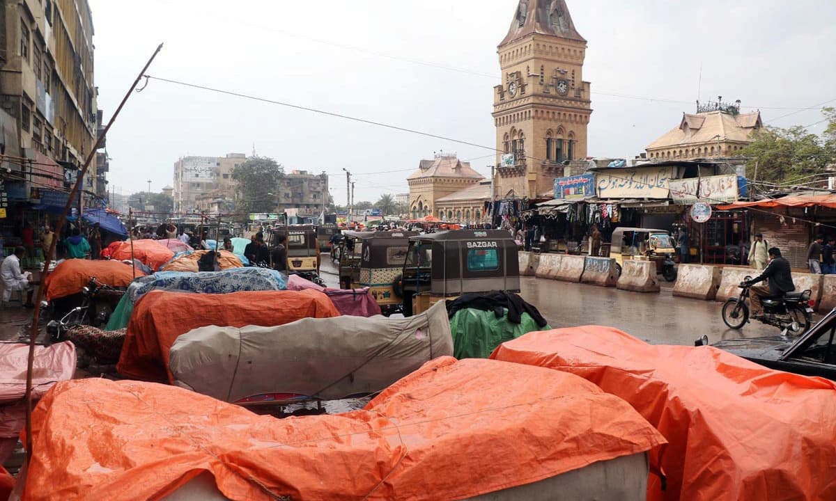 Vendors cover items on their handcart during rain in the port city. —Online