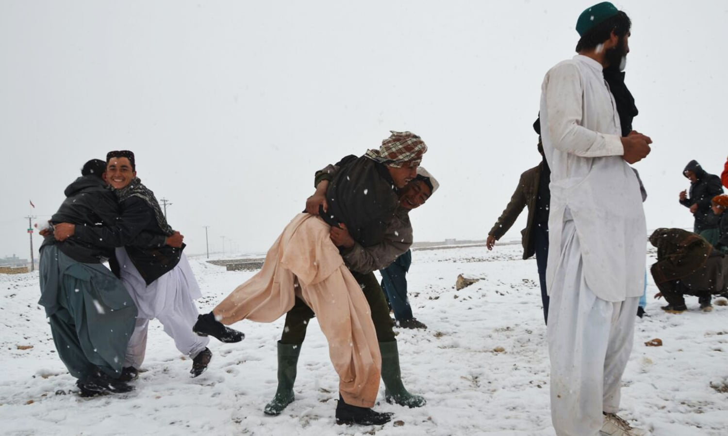 Men wrestle in the snow as Quetta residents celebrate the colder weather.— Photo by Asmatullah Kakar