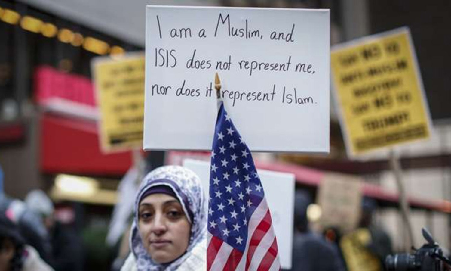 A Muslim woman holds a poster condemning ISIS at a protest.—AFP