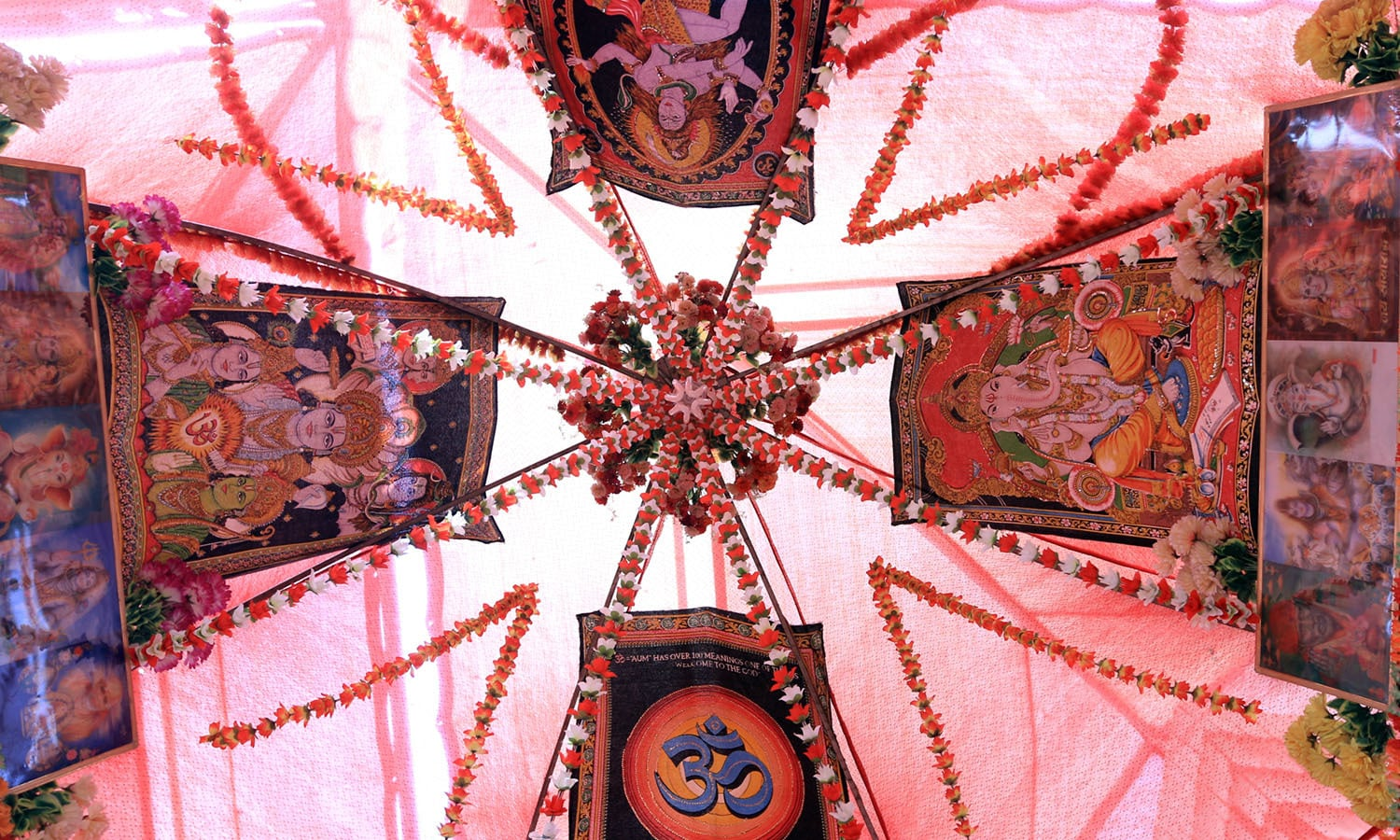 The venue decorated with flowers and images of Hindu deities.