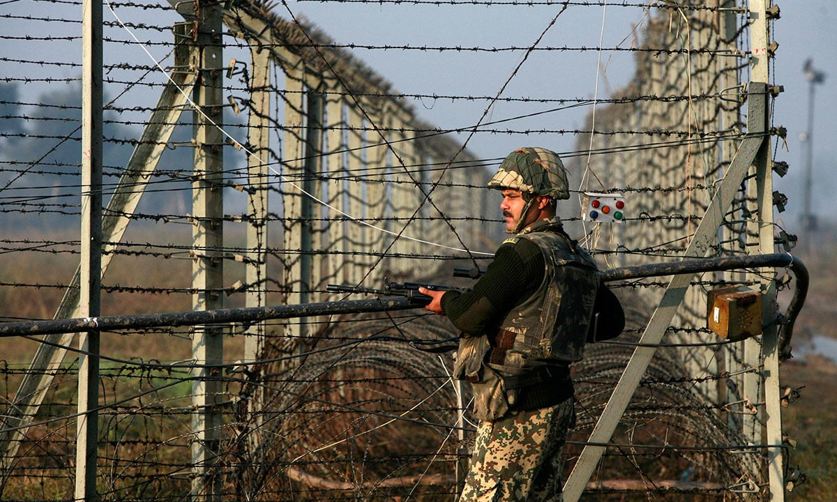 An Indian Border Security Force soldier patrols the fenced border with Pakistan in Suchetgarh, located southwest of Jammu and Kashmir | Reuters